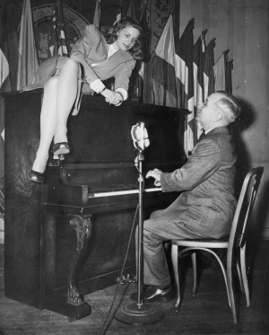 Vice President Harry S. Truman plays as Lauren Bacall lounges on the piano in February 1945.