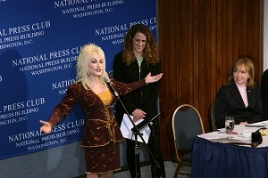 Dolly Parton addresses the luncheon as NPC President Donna Leinwand and Tennessee's commissioner of tourism, Susan Whittacre, look on.