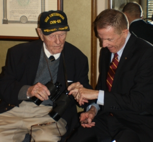 Midway veteran Jack Crawford shows Post 20 Commander Jim Noone his Legion binoculars.