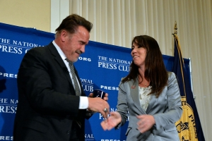 Former California governor and actor Arnold Schwarzenegger receives a National Press Club all-purpose mug from Club President Alison Fitzgerald Kodjak.