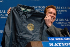 Then-California Gov. Arnold Schwarzenneger shows off a National Press Club windbreaker after speaking at the Club in 2007.
