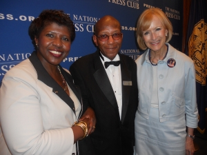 Fans Gwen Ifill and Judy Woodruff, PBS anchors, flank head table waiter Andrew Price on July 24 at the final luncheon of his 45-year career.