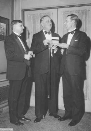 FDR receives his National Press Club membership card from President Raymond Brandt prior to the black-tie dinner in 1933.  Former Club President Theodore Tiller of The Washington Times is on the left.
