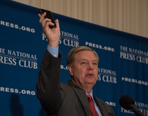 Senator Lindsey Graham, Republican candidate for President, speaking at a September 8, 2015 National Press Club luncheon, shows off his new smartphone. It replaces one for which Donald Trump gave out the number.