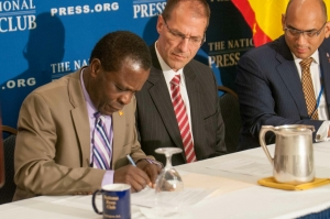 Grenada Prime Minister Keith C. Mitchell signs agreement with Carbon War Rooms at the National Press Club, April 11, 2014.