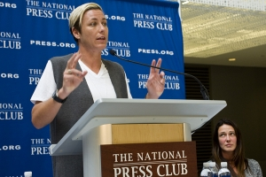 Soccer star Abby Wambach speaks about her retirement and gender inequality in sports at an October 28, 2015 National Press Club luncheon. Seated, right, is Sarah Huffman, Wambach's wife.