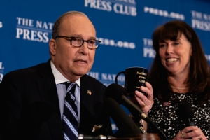 Larry Kudlow, White House National Economic Council Director, receives a National Press Club coffee mug, from Club President Alison Fitzgerald Kodjak at an April 23 Headliners luncheon.