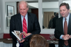 Former White House Press Secretary Mike McCurry (left) leafs through the book presented to him to by Tom McMahon, chair of the National Press Club Communications and Marketing Committee, following his April 10, 2014, dinner talk to the committee.