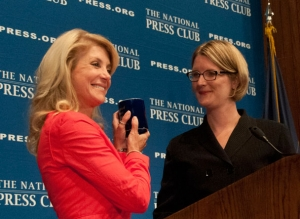 Texas State Senator Wendy Davis displays the new NPC coffee mug presented to her following her August 5, 2013, luncheon address to the National Press Club by President Angela Greiling Keane