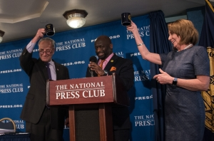 Senate Democratic Leader Chuck Schumer (left) and House Democrat                                                                                                                                                                                                                       ic Leader Nancy Pelosi hoist National Press Club mugs given them by Club President Jeffrey Ballou (center) following their appearamce at an NPC Newsmaker Feb. 27.