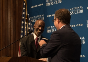 Rev. John Richard Bryant, left, receives National Press Club mug from Club President John Hughes at conclusion of his luncheon speech August 12.