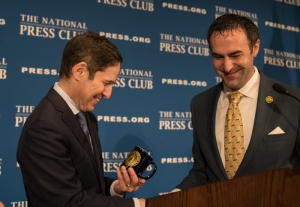 The complete set: Centers for Disease Control director Tom Frieden admires the National Press Club coffee mug presented to him by NPC President Tommy Burr following his luncheon address to the Club, May 26, 2016. He has a growing collection of NPC coffee mugs, since this is the fourth time he has spoken at a Club luncheon.