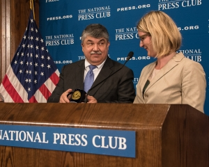 AFL-CIO President Richard Trumka thanks former NPC President Angela Greiling Keane for the souvenir NPC coffee mug, pointing out that it was made in China, at a National Press Club Luncheon on April 4, 2017.