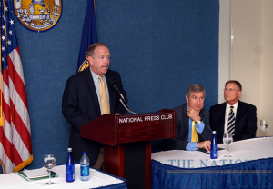 Mark Schoeff Jr., NPC Newsmakers Committee chair (podium), introduces Georgia State University's President Mark Becker (center) and inaugural football Coach Bill Curry (far right) at a September 23, 2009 Newsmaker...