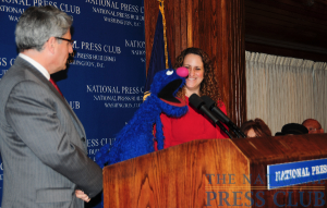 Sesame Street Muppet Grover answers a question from the audience as Sesame Workshop President and CEO Gary Knell and National Press Club President Donna Leinwand look on.Photo: Al Teich