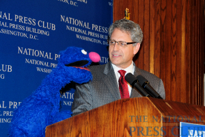 Guest speaker Gary Knell is joined at the podium by Grover, one of the original Sesame Street muppets, at a December 8, 2009 luncheon.Photo: Al Teich