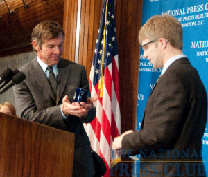 Dennis Quaid admires the souvenir NPC coffee mug presented to him following his address by Press Club president Alan Bjerga.Photo: Al Teich