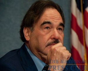 Director Oliver Stone looks on as Club President Alan Bjerga introduces him before his talk.Photo: Al Teich