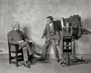 George Harris (right) prepares to take a photo of political cartoonist Clifford Berryman in the Harris & Ewing studio across F Street from the National Press Building circa 1915.