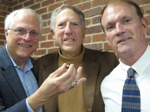 Gil Klein, (left) chairman of the National Press Club's History and Heritage Team, accepts the ring of the Club's 1913 president, Oswald F. Schuette, during a talk about Schuette's life.  Presenting the ring were Schuette's biographer, James Castellan (center) and his grandson, James F. Schuette, Jr. Oswald was the earliest president to receive the ring, and it is exactly the same as the one Klein is wearing as the 1994 president.