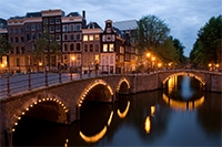 A view of Amsterdam with the Reguliersgracht on the corner with the Keizersgracht at dusk.